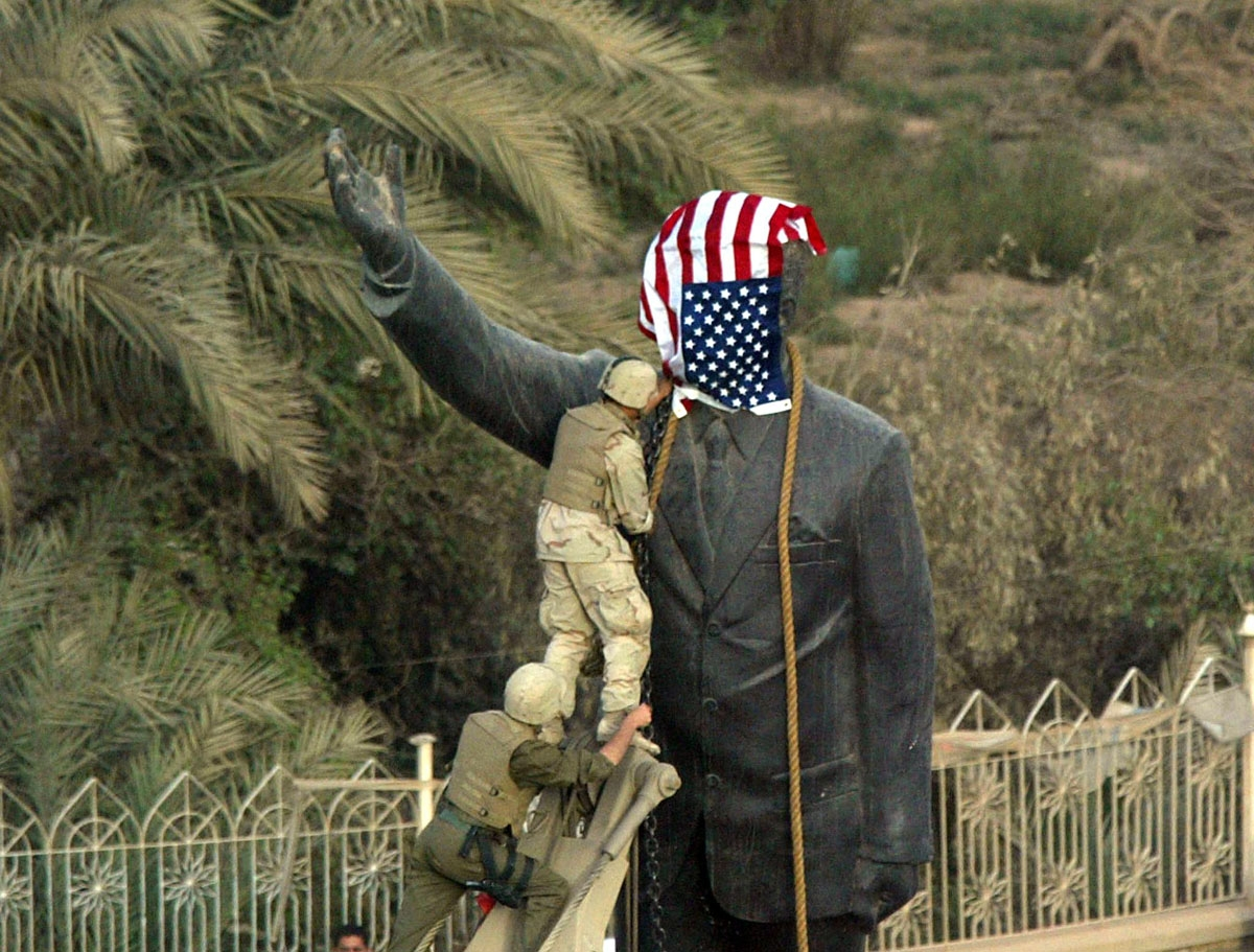 US Marines cover the statue of Iraqi President Saddam Hussein with the US flag in Baghdad's al-Fardous street 09 April 2003 as they prepare to bring it down. They removed it shortly afterwards and replaced it with an old Iraqi flag.