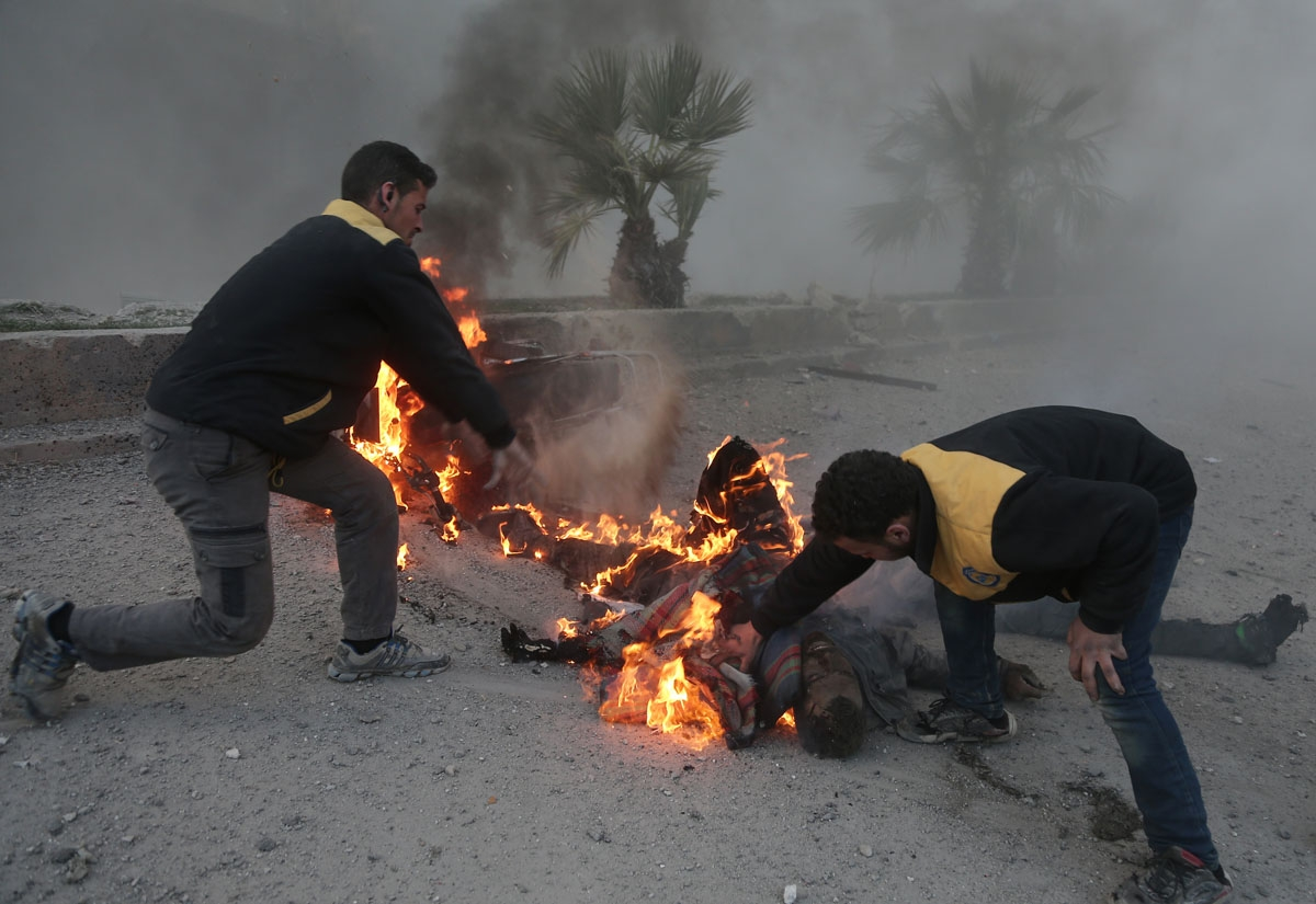 Syrian civil defence volunteers try to put out a fire engulfing a man fatally wounded  in the bombardment of the rebel-held town of Hamouria, in the besieged Eastern Ghouta region on the outskirts of the capital Damascus, on March 7, 2018.