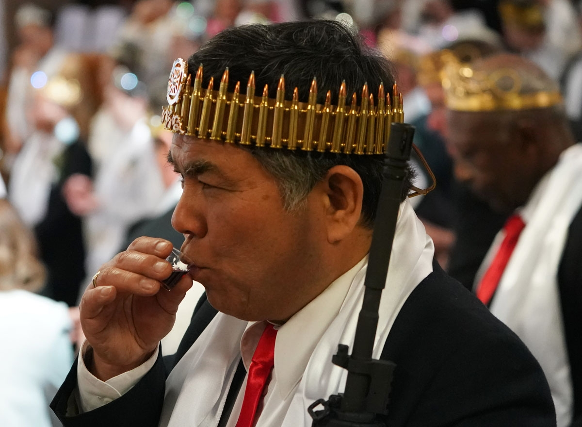 A man wearing a crown of rifle shells, takes communion, as worshippers at World Peace and Unification Sanctuary attend services February 28, 2018 in New Foundland, Pennsylvania.