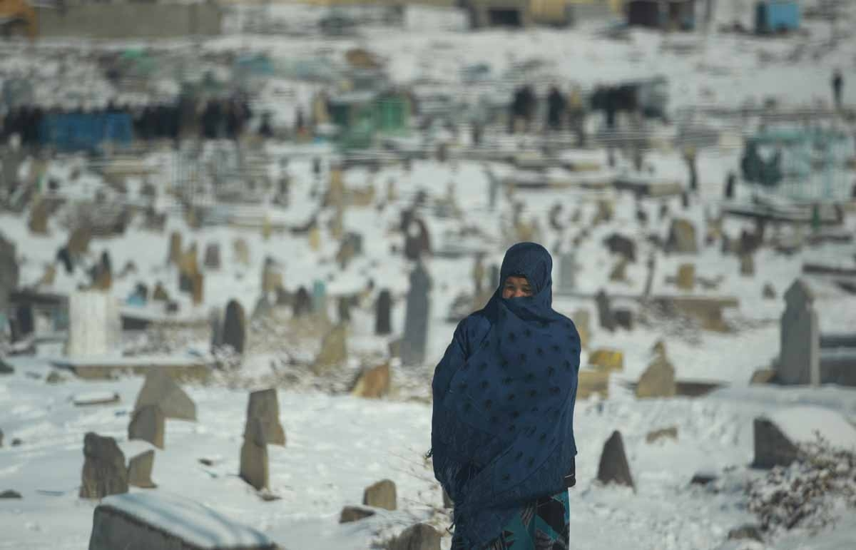 An Afghan resident wrapped in a shawl walks past a snow-covered cemetery in Kabul on January 9, 2014. As winter sets in across Central Asia, many Afghans struggle to provide adequate food and shelter for their families.