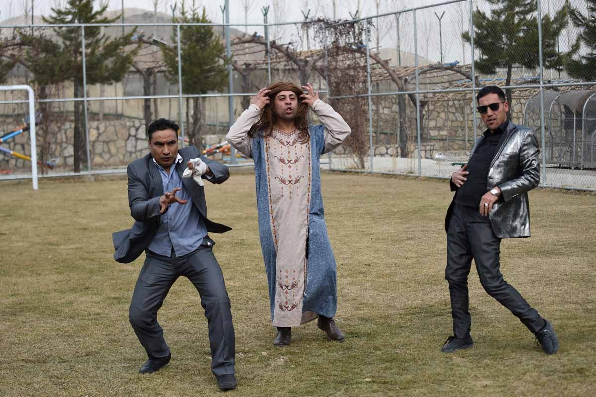 In this photograph taken on March 6, 2017, Afghan comedian Ibrahim Abed (L), Gholam Nabi Roashan (R) and Ahmad Siar Matin (C) perform a song while filming the comedy television show Shabak-e-Khanda on the outskirts of Kabul.