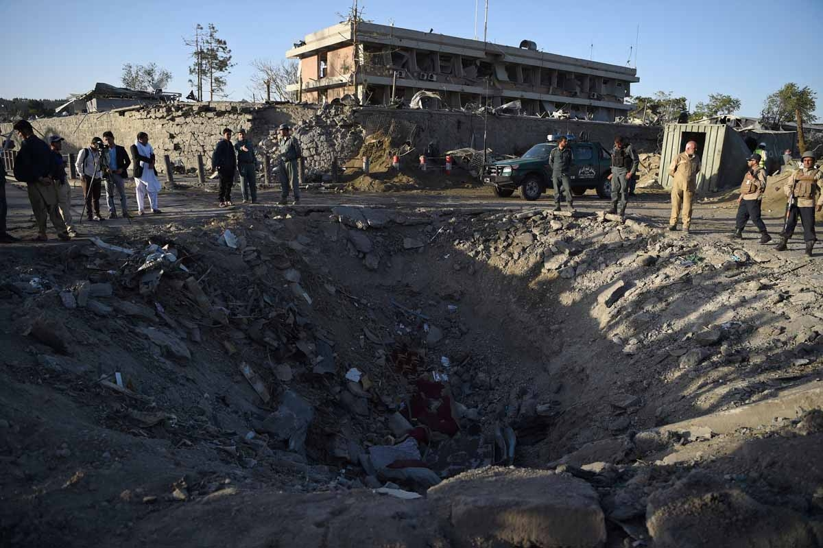 Afghan security forces and residents stand near the crater left by a truck bomb attack in Kabul on May 31, 2017.