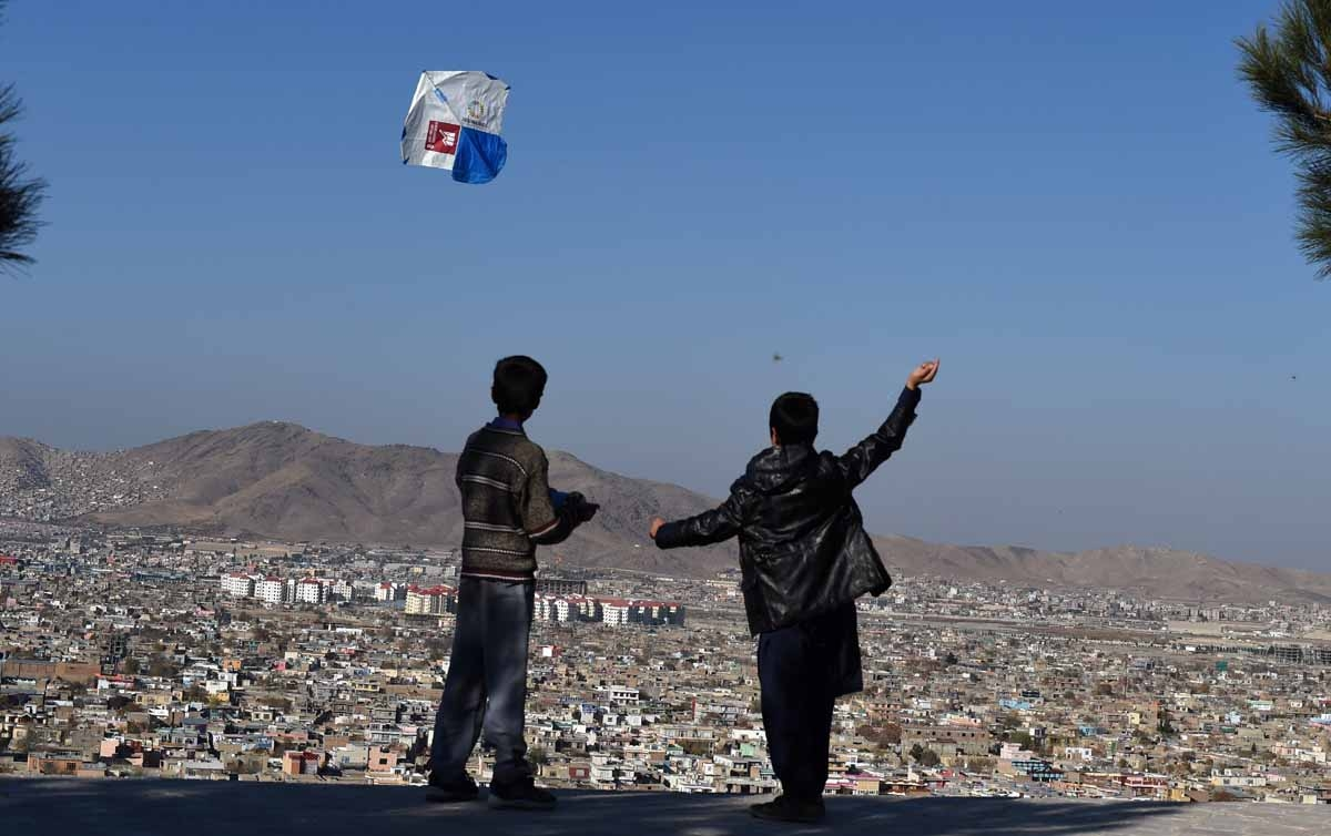 Afghan children fly kites during a kite festival at the Wazir Akbar Khan hilltop in Kabul on November 26, 2016.