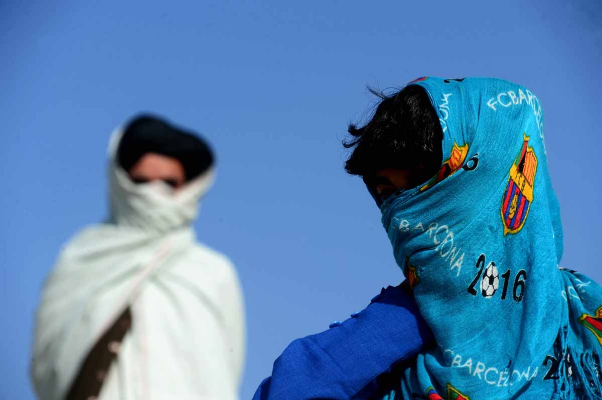 This file photo taken on October 31, 2016 shows an Afghan boy (R), who was held as a child sex slave, as he walks with a relative at a unidentified location in Afghanistan.