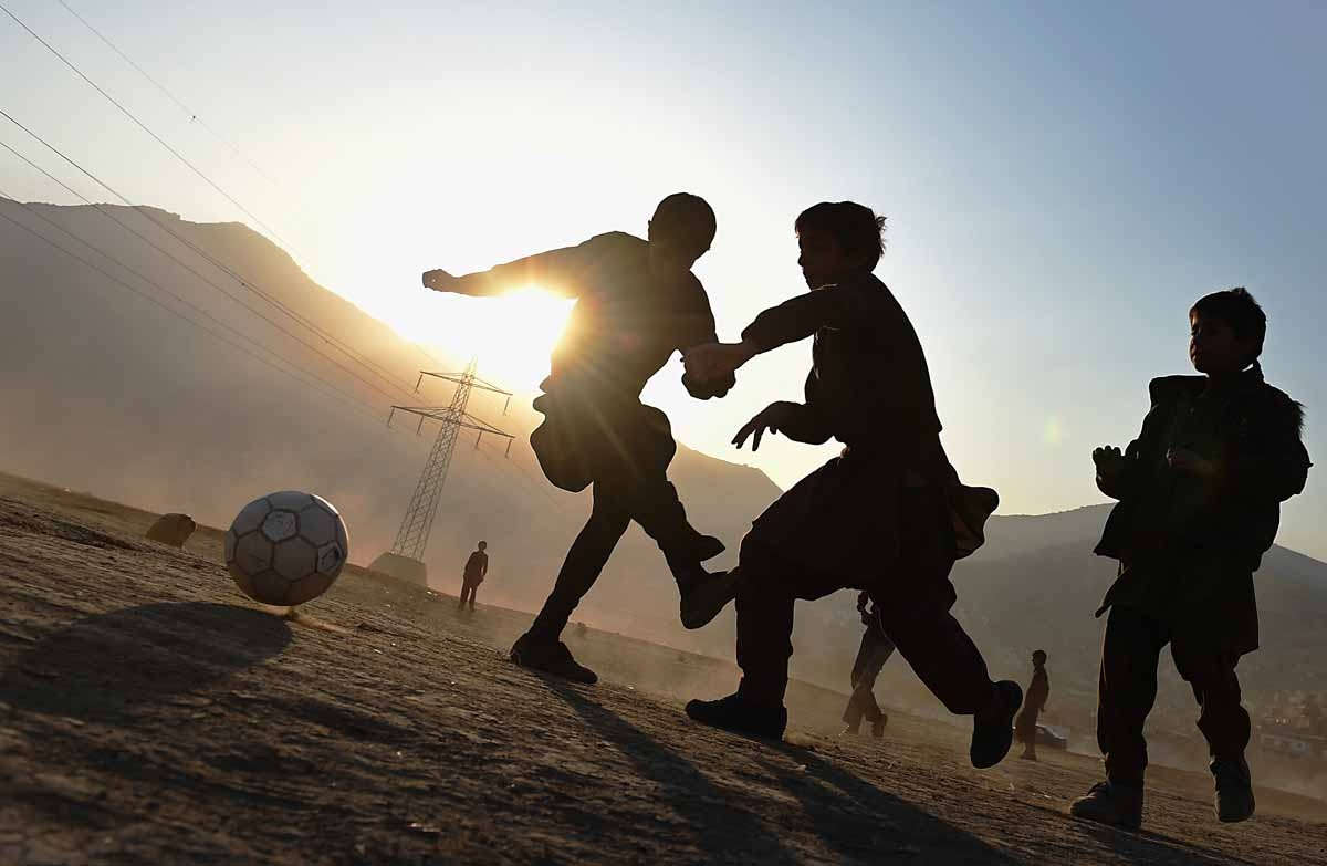 Afghan children play football in a field in Kabul on November 23, 2014. Football is one of the most popular games in Afghanistan and is played on dusty dry ground more often than grass. AFP PHOTO/SHAH Marai / AFP PHOTO / SHAH MARAI