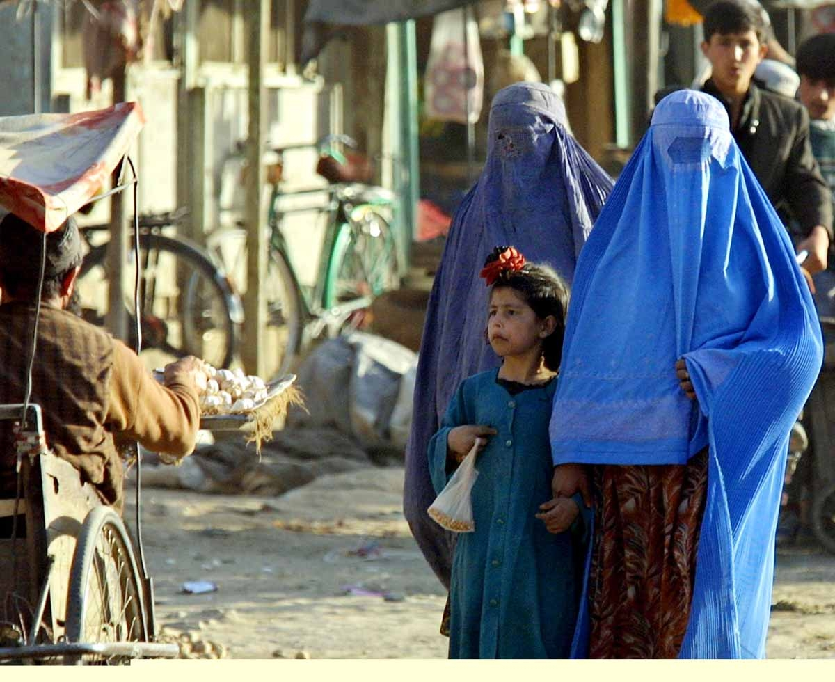 Afghani women walk in Kabul, 14 November 2001. It was forbidden for women to appear outdoors without close male relatives just a few days ago, before the capture of the city by the Northern Alliance forces 13 November.