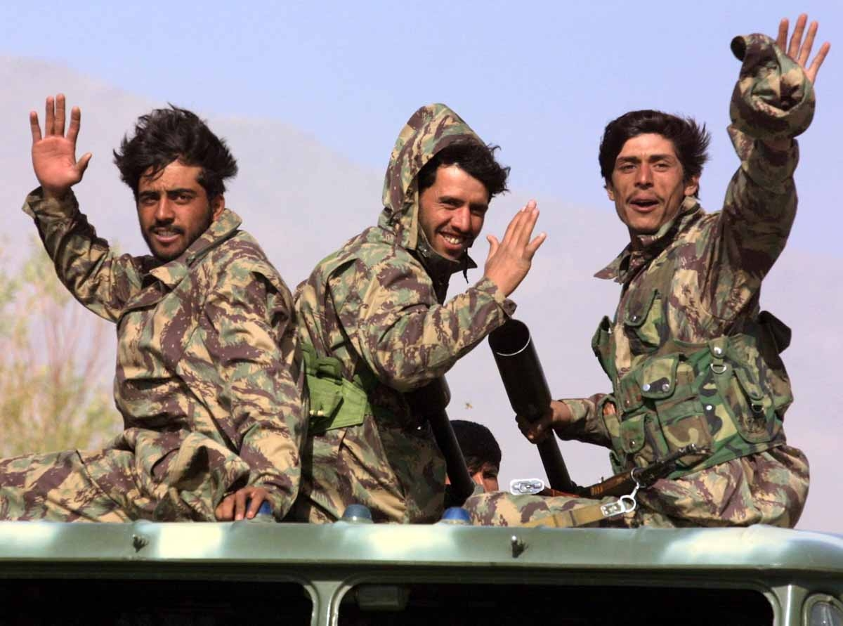 Northern Alliance soldiers wave, moving to a front line, 12 November 2001, passing by the town of Baghram, some 25 kms north from Kabul.