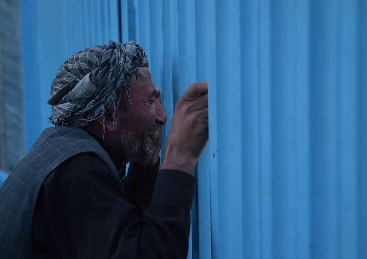An Afghan man who lost his father in a gunmen attack weeps at the main gate of the Karte Sakhi shrine in Kabul on October 12, 2016.