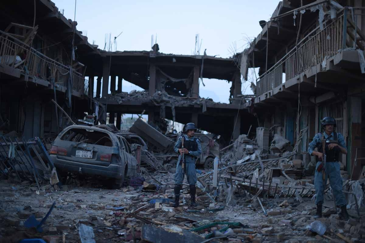 Afghan policemen stand guard at a market destroyed by a powerful truck bomb in Kabul on August 7, 2015.