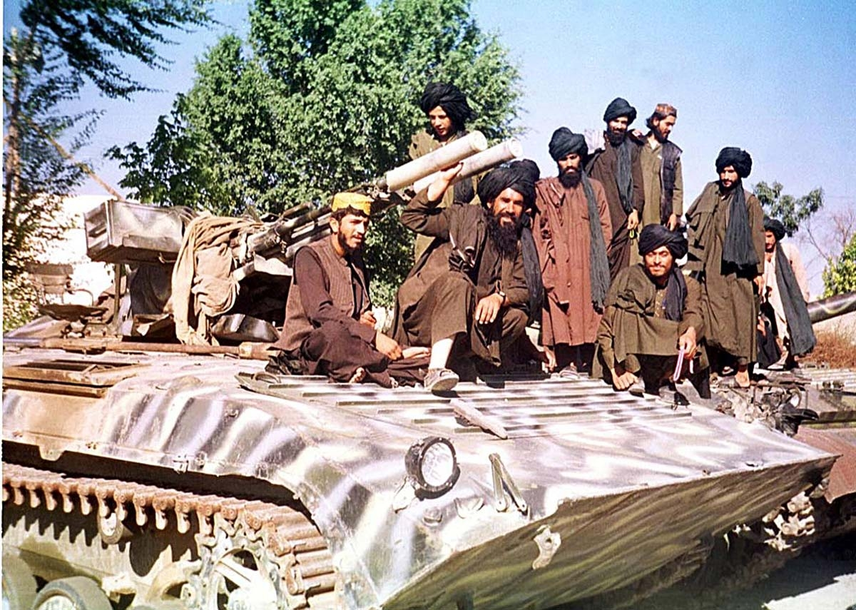 Taliban fighters sit on top of a tank near Kabul 04 October 2001. The Taliban are beefing up security in most parts of the country including Kabul in preparation for defending a US possible assault.