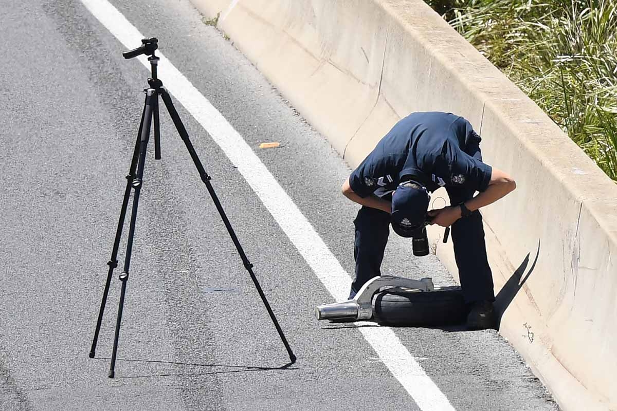A policeman photographs a plane wheel on the freeway of a Beechcraft plane after it crashed into a shopping centre just after take-off from the Essendon airport in Melbourne on February 21, 2017.
