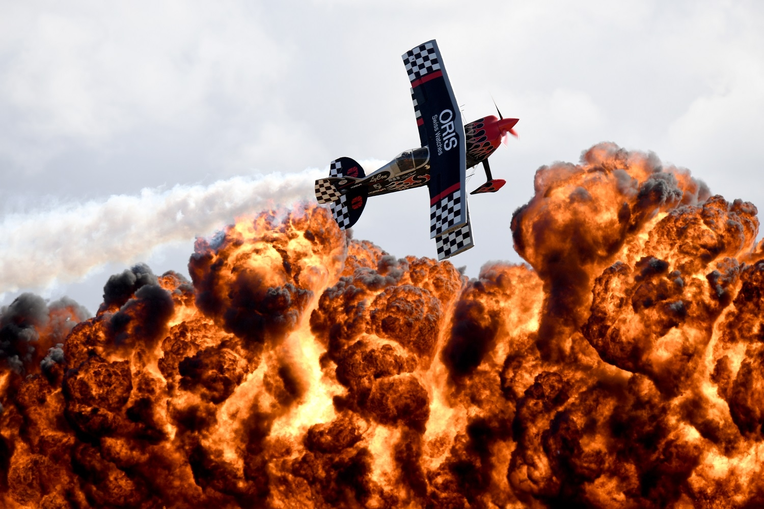 A member of the Tinstix of Dynamite aerobatics team flies in front of a wall of fire during the Australian International Airshow in Melbourne on March 5, 2017.