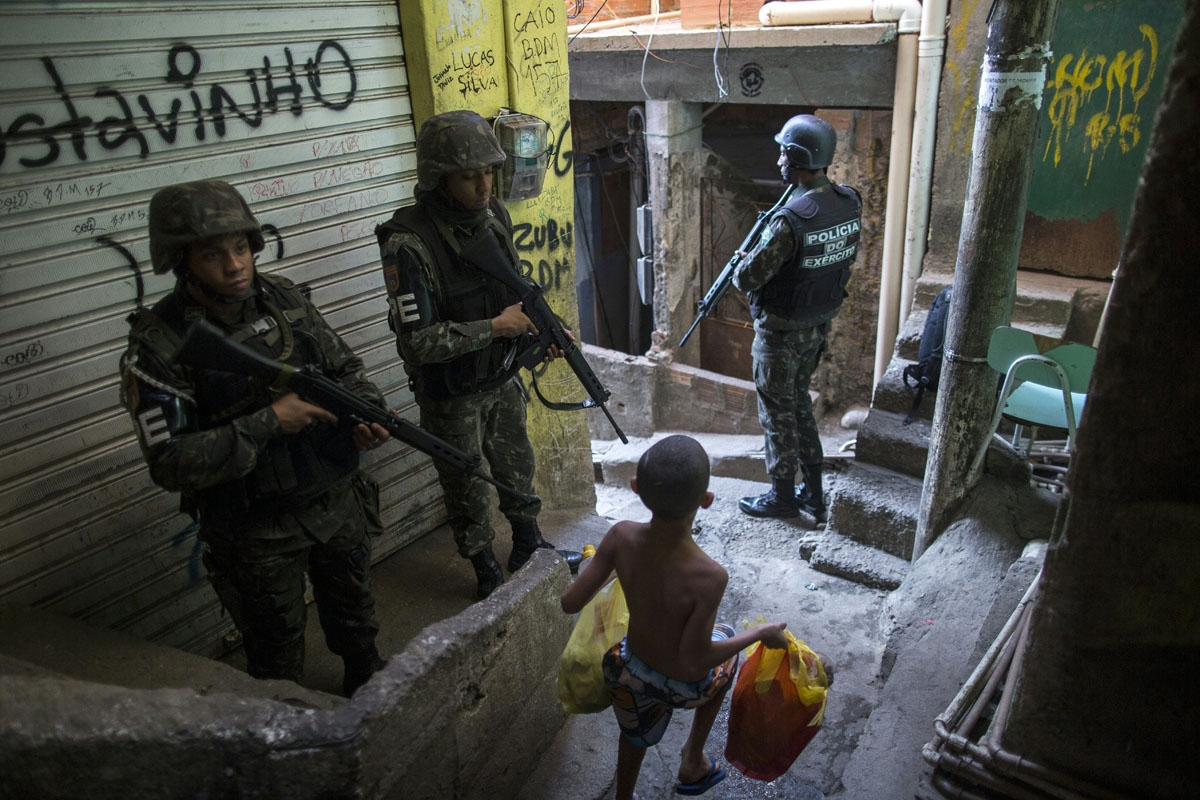 Employing urban combat tactics, Brazilian army military police personnel patrol along an alley in the Rocinha favela in Rio de Janeiro, Brazil on September 25, 2017.  Security officials said the giant Rocinha favela in Rio de Janeiro was back under contro