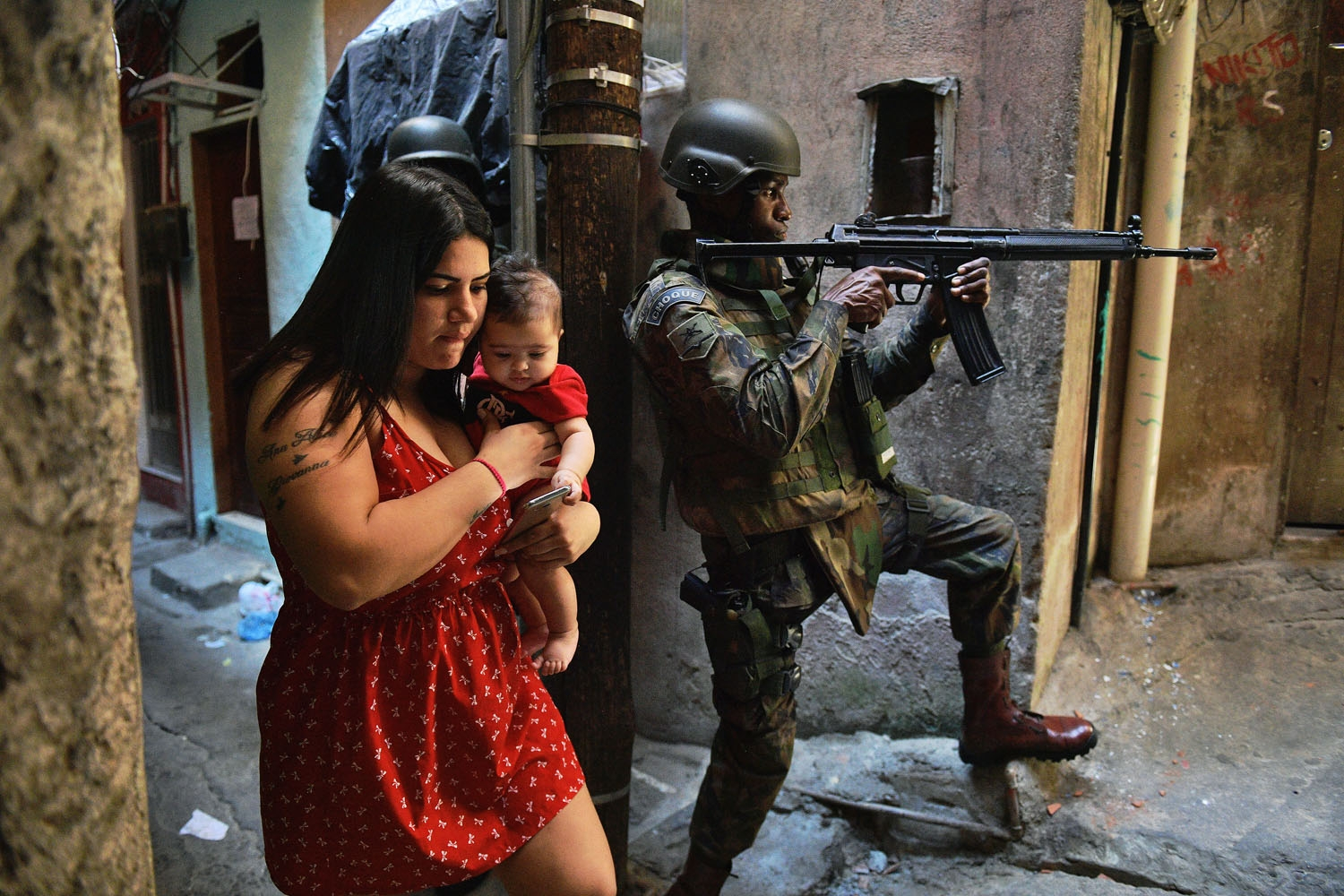 A woman walks with her baby past a PM militarized police soldier in position and aiming his rifle in Rocinha favela in Rio de Janeiro, Brazil on September 23, 2017.  Although shooting was reported in the early hours of Saturday in Rocinha -- for the seven