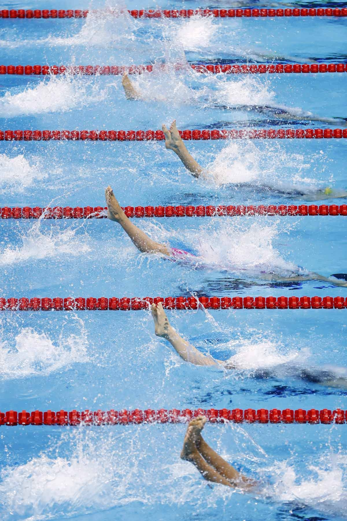 Swimmers compete in the Women's 100m Backstroke heats during the swimming event at the Rio 2016 Olympic Games at the Olympic Aquatics Stadium in Rio de Janeiro on August 7, 2016.
