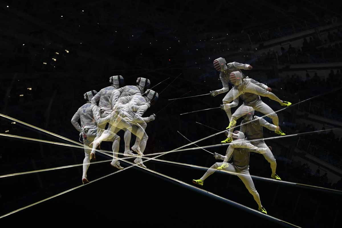 A multi exposure picture shows Russia's Artur Akhmatkhuzin (L) competing against US Alexander Massialas during their men's individual foil qualifying bout as part of the fencing event of the Rio 2016 Olympic Games, on August 7, 2016, at the Carioca Arena