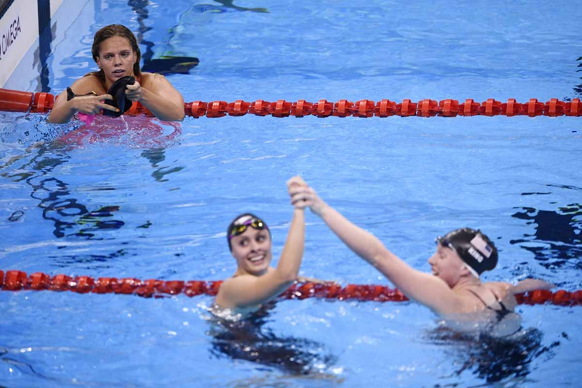 Russia's Yulia Efimova (L) looks on USA's Lilly King (R) celebrates winning the Women's 100m Breaststroke Final with USA's Katie Meili during the swimming event at the Rio 2016 Olympic Games at the Olympic Aquatics Stadium in Rio de Janeiro on August 8, 2
