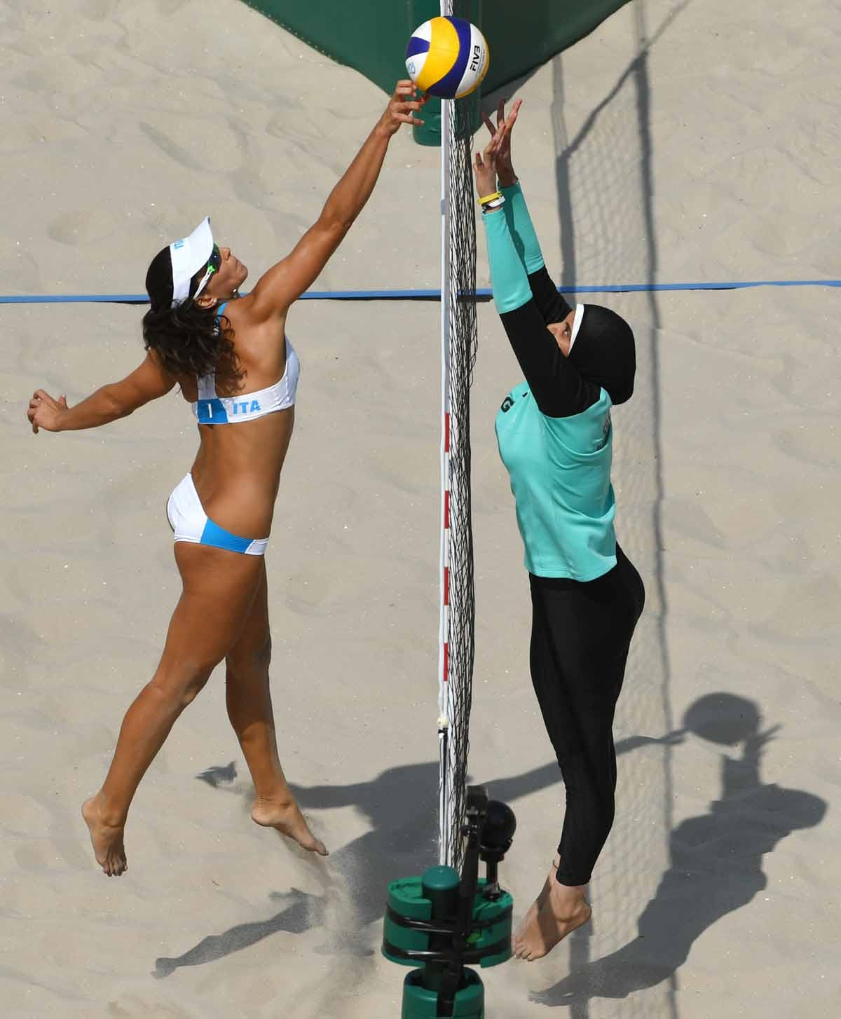 Italy's Marta Menegatti (L) jumps for the ball during the women's beach volleyball qualifying match between Italy and Egypt at the Beach Volley Arena in Rio de Janeiro on August 9, 2016, for the Rio 2016 Olympic Games.