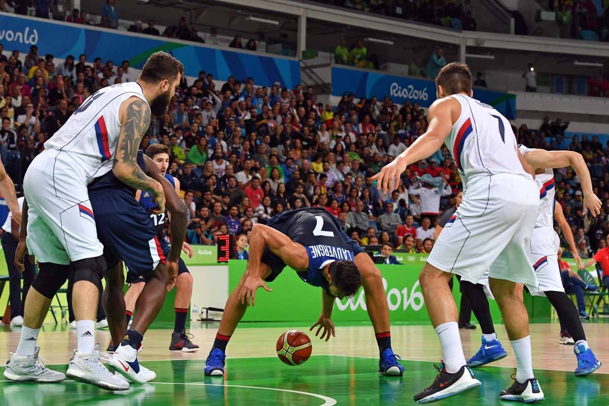 France's power forward Joffrey Lauvergne (C) fails to catch the ball during a Men's round Group A basketball match between Serbia and France at the Carioca Arena 1 in Rio de Janeiro on August 10, 2016 during the Rio 2016 Olympic Games.