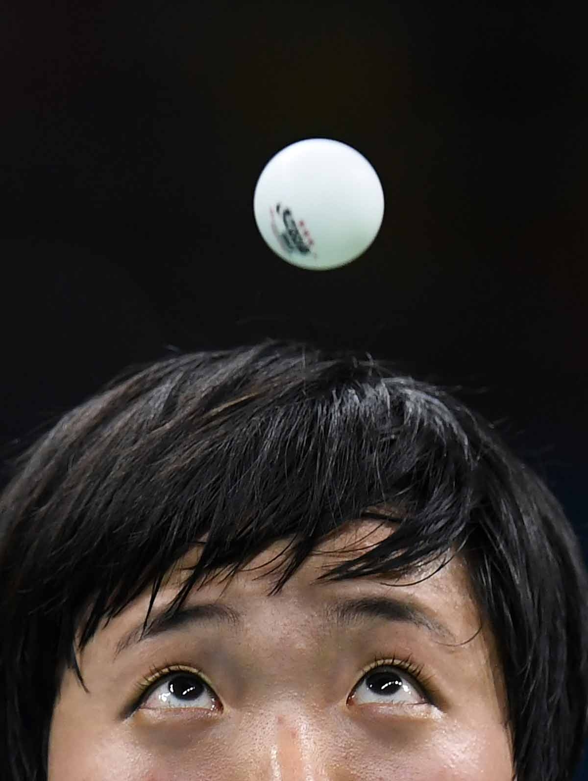 North Korea's Kim Song I eyes the ball as she serves against Japan's Ai Fukuhara in their women's singles bronze medal table tennis match at the Riocentro venue during the Rio 2016 Olympic Games in Rio de Janeiro on August 10, 2016.