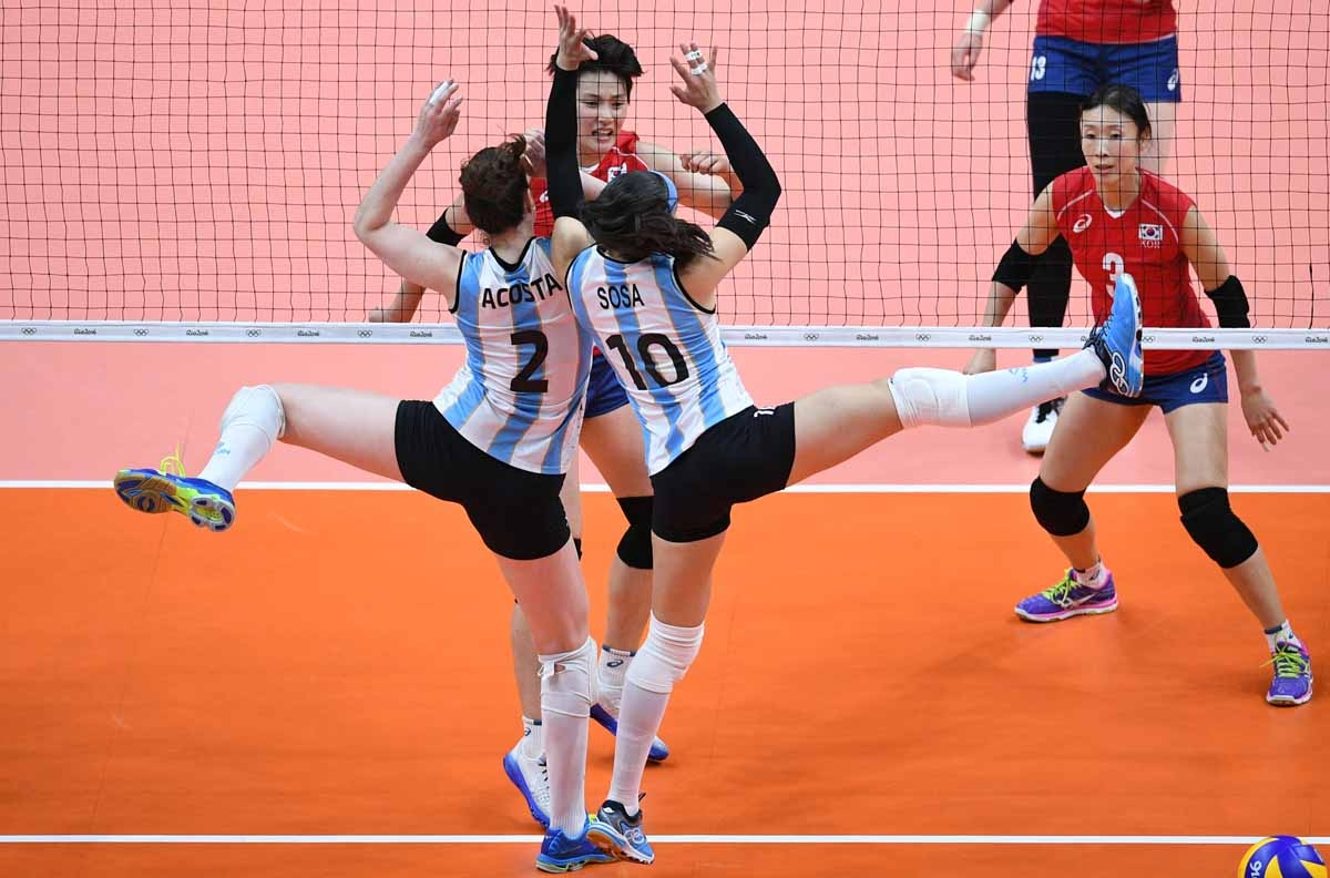 Argentina's Tanya Acosta (C-L) and Emilce Sosa try to block the ball during the women's qualifying volleyball match between South Korea and Argentina at the Maracanazinho stadium in Rio de Janeiro on August 10, 2016, during the Rio 2016 Olympic Games.