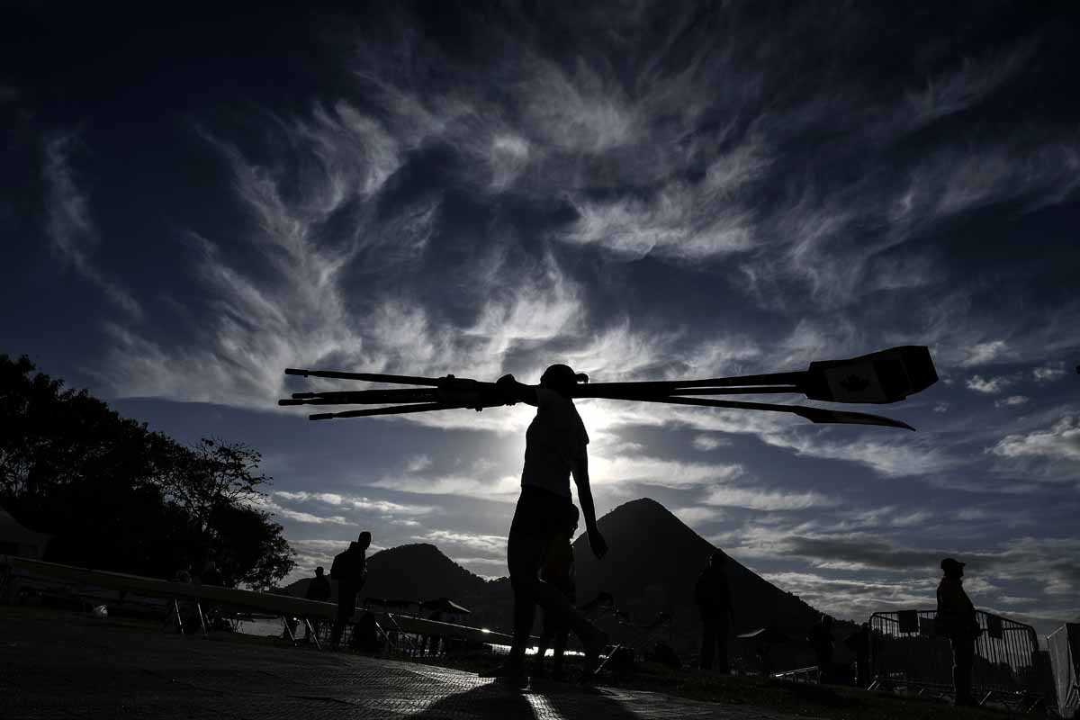 A rowers carries oars as he arrives for a training session at the Lagoa stadium during the Rio 2016 Olympic Games in Rio de Janeiro on August 11, 2016.