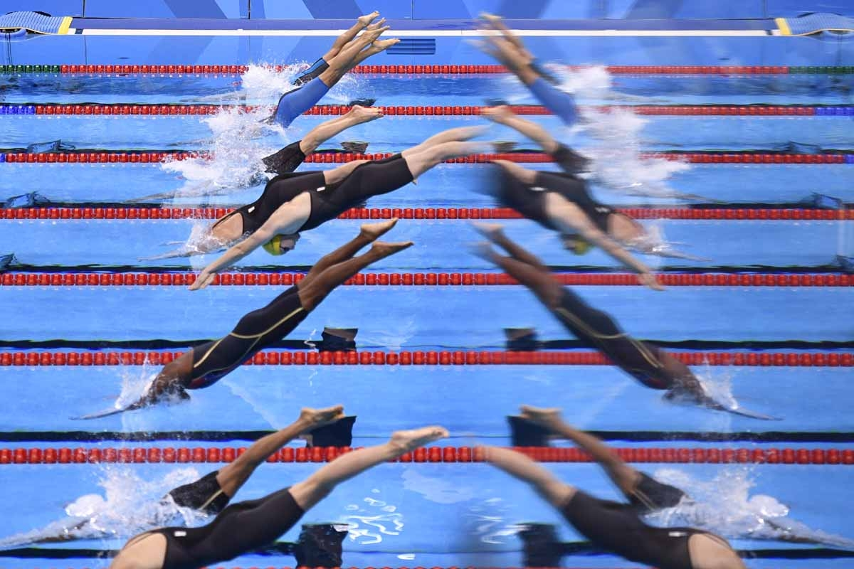 Atletes are mirrored in a window during the Women's 50m Freestyle heats at the swimming event at the Rio 2016 Olympic Games at the Olympic Aquatics Stadium in Rio de Janeiro on August 12, 2016.