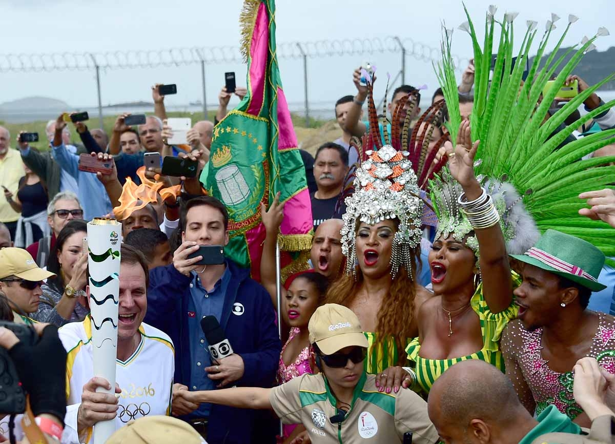 Mayor of Rio Eduardo Paes (L) carries the Olympic torch next to dancers from the Mangueira Samba School, ahead of the Rio 2016 Olympic Games in Rio de Janeiro on August 3, 2016