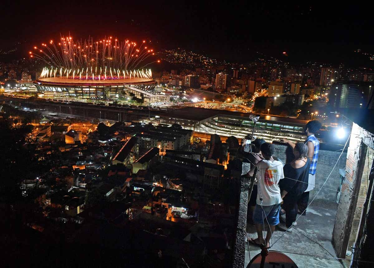 People watch fireworks exploding over the Maracana stadium, from a terrace in the favela Mangueira, during the opening ceremony of the Rio 2016 Olympic Games in Rio de Janeiro on August 5, 2016