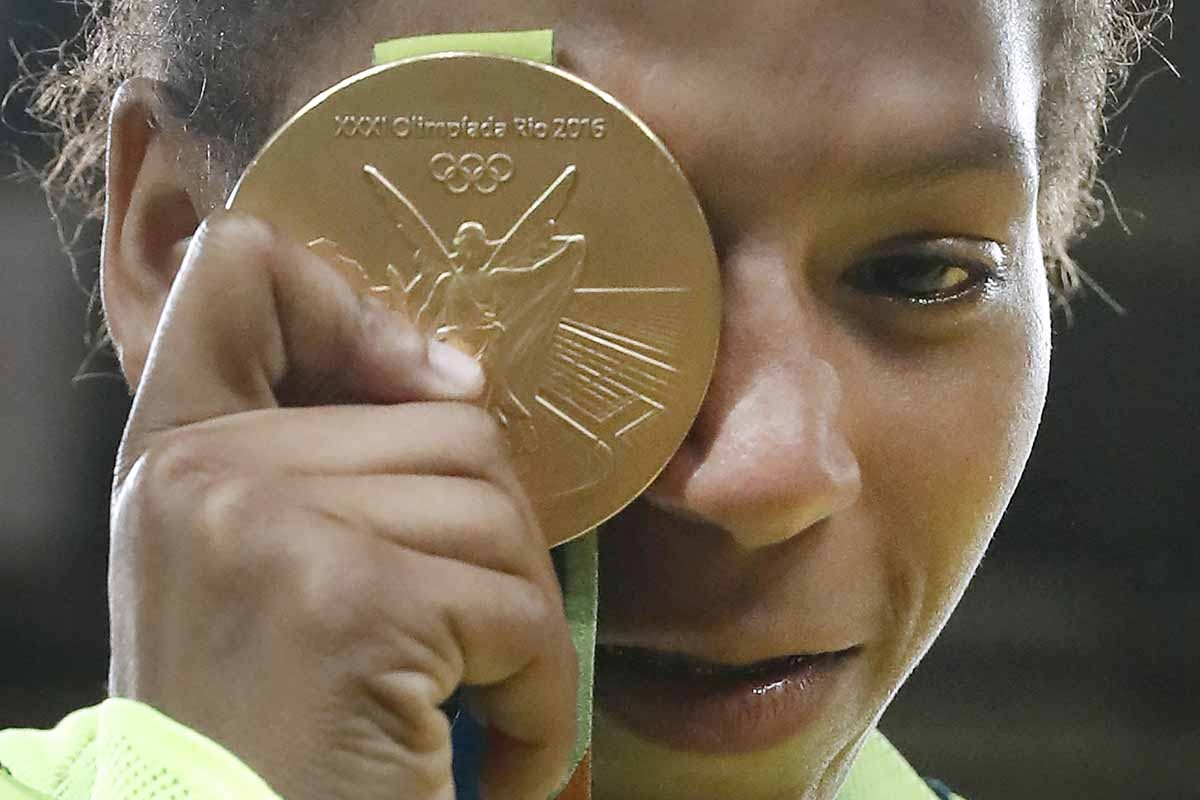 Brazil's Rafaela Silva celebrates with her gold medal following the women's -57kg judo contest of the Rio 2016 Olympic Games in Rio de Janeiro on August 8, 2016.