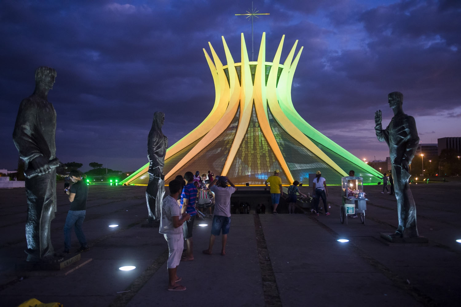 Tourists are seen among the bronze statues of the four evangelists in front of the Cathedral in Brasilia on June 30, 2014