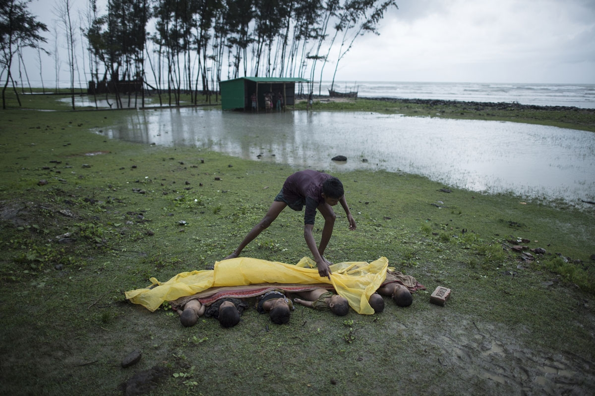 / This photo taken on September 28, 2017 shows a man covering the bodies of Rohingya Muslim refugee children, lined up near the shore of Inani beach, near Cox's Bazar after their boat capsized.
