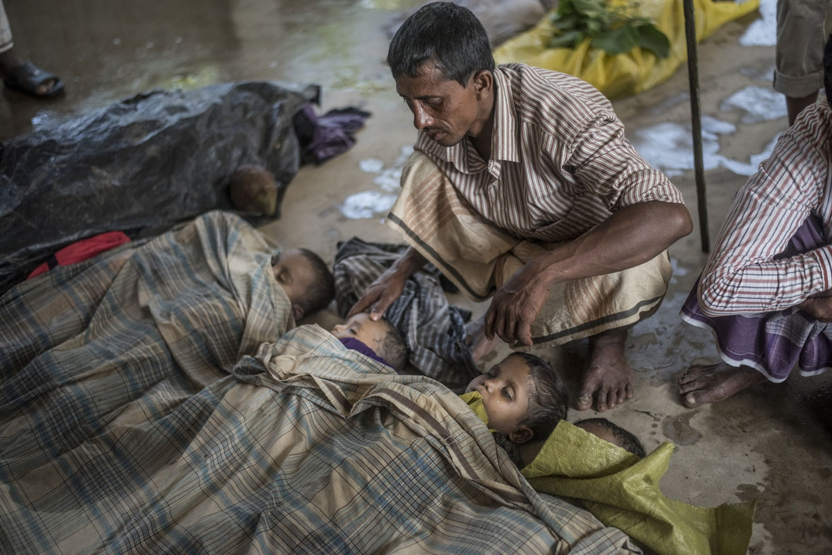 A Rohingya Muslim refugee mourns beside the bodies of his three children at a school near Inani beach in Cox's Bazar district on September 29, 2017.