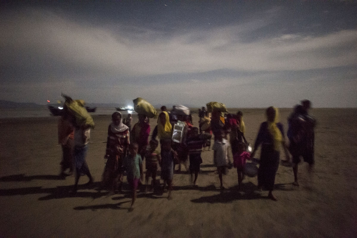 Rohingya Muslim refugees walk by night after crossing the border from Myanmar, on the Bangladeshi shores of the Naf river in Teknaf on September 29, 2017.