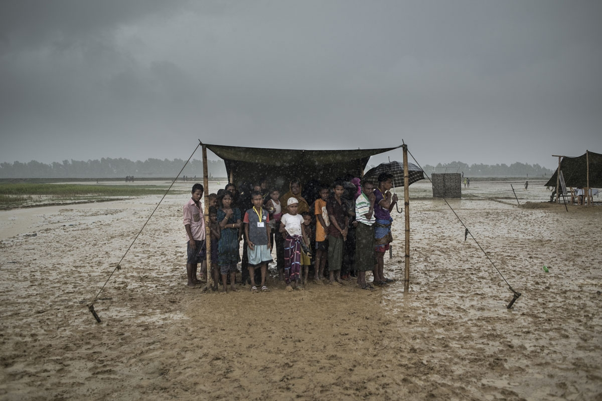 Rohingya Muslim refugees take shelter from the rain during a food distribution at Nayapara refugee camp in Bangladesh's Ukhia district on October 6, 2017.