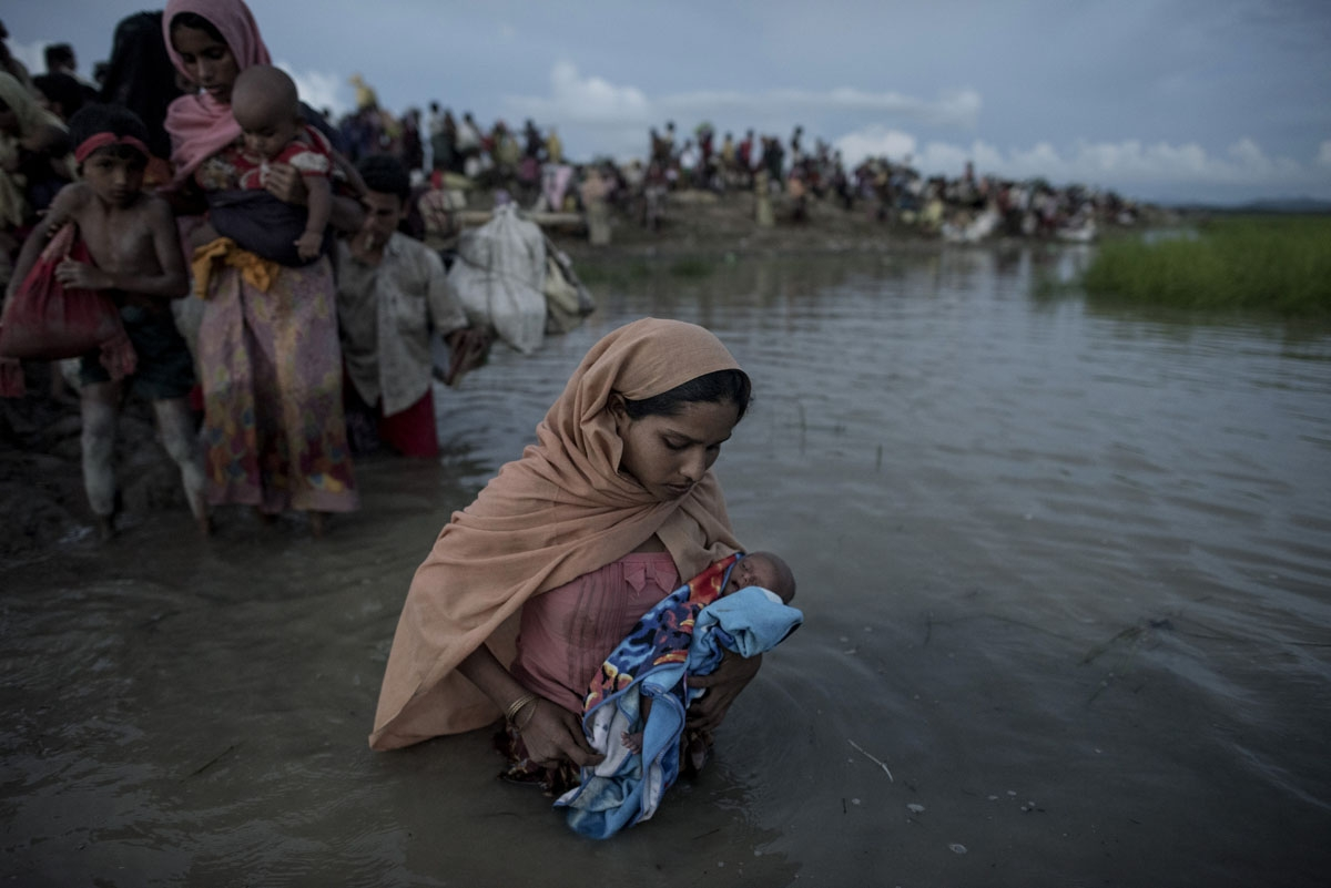 Rohingya refugees wade while holding a child after crossing the Naf river from Myanmar into Bangladesh in Whaikhyang on October 9, 2017.  A top UN official said on October 7 Bangladesh's plan to build the world's biggest refugee camp for 800,000-plus Rohi