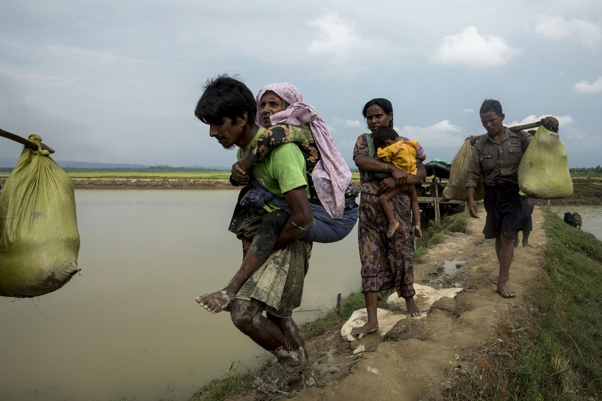 Displaced Rohingya refugees from Rakhine state in Myanmar walk near Ukhia, at the border between Bangladesh and Myanmar, as they flee violence on September 4, 2017.