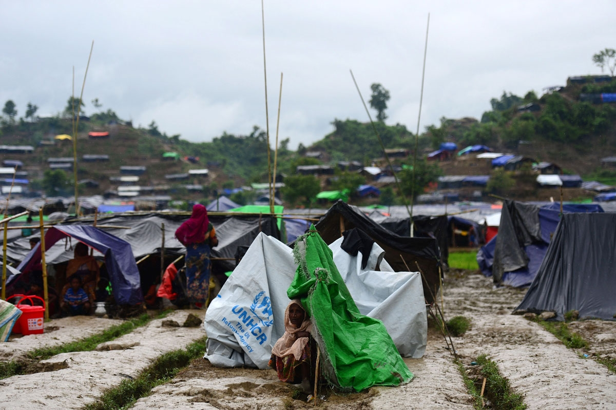 A Rohingya refugee woman sits next to a newly built makeshift shelter in a camp in the Bangladeshi locality of Ukhia on September 9, 2017. Nearly 300,000 Rohingya have fled violence churning through Rakhine state into Bangladesh, the United Nations said o