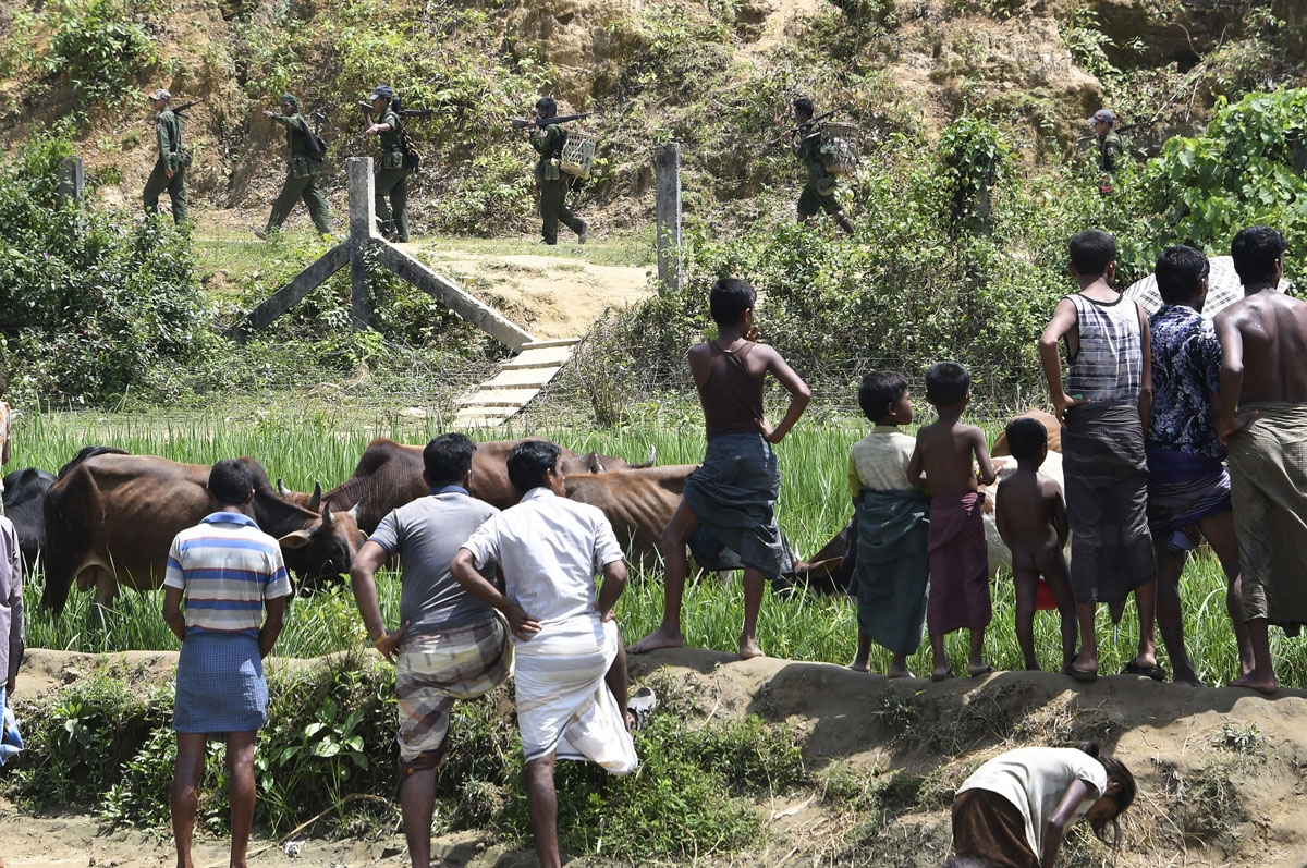 Rohingya Muslim refugees in Jalpatoli refugee camp in the no-man's land area between Myanmar and Bangladesh watch as Myanmar soldiers patrol on the other side of the border, near Gumdhum village in Ukhia on September 16, 2017.