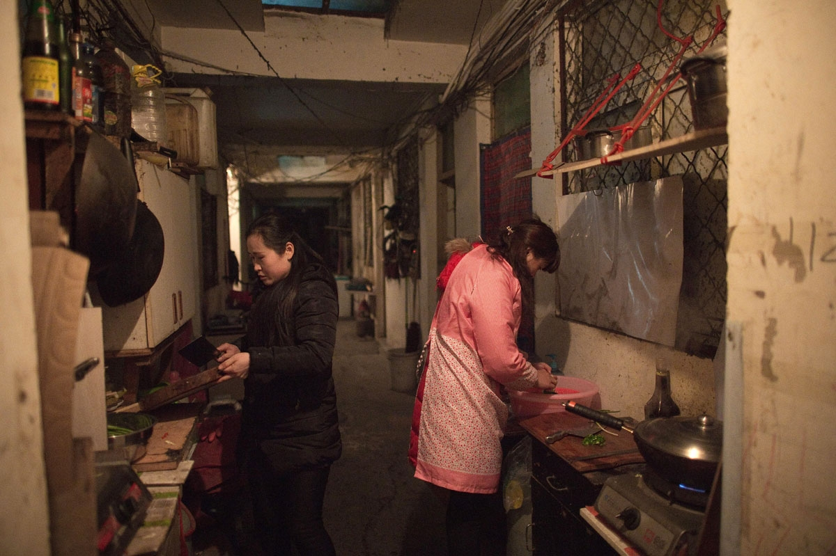 This picture taken on February 15, 2017 shows women cooking in the corridor, where they share a stove and a sink with their neighbours, of a building in the Heiqiaocun migrant village in Beijing.
