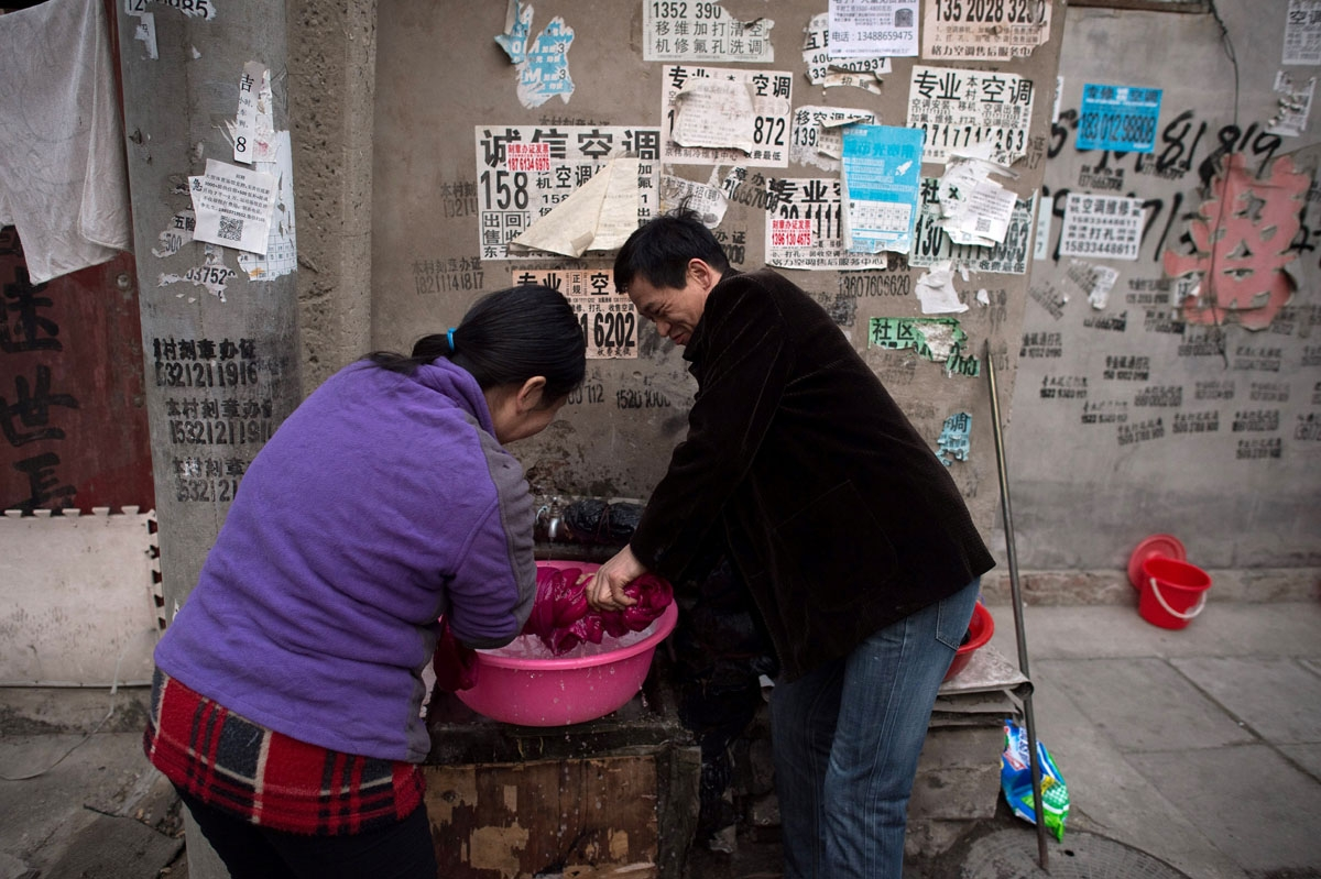 This picture taken on February 15, 2017 shows a man helping a woman to wring a coat dry in the Heiqiaocun migrant village in Beijing.