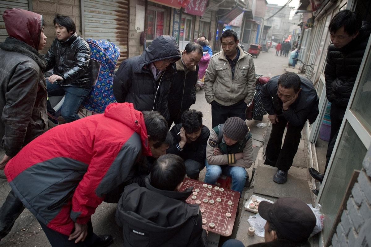 This picture taken on February 15, 2017 shows people playing Chinese chess in the Heiqiaocun migrant village in Beijing.