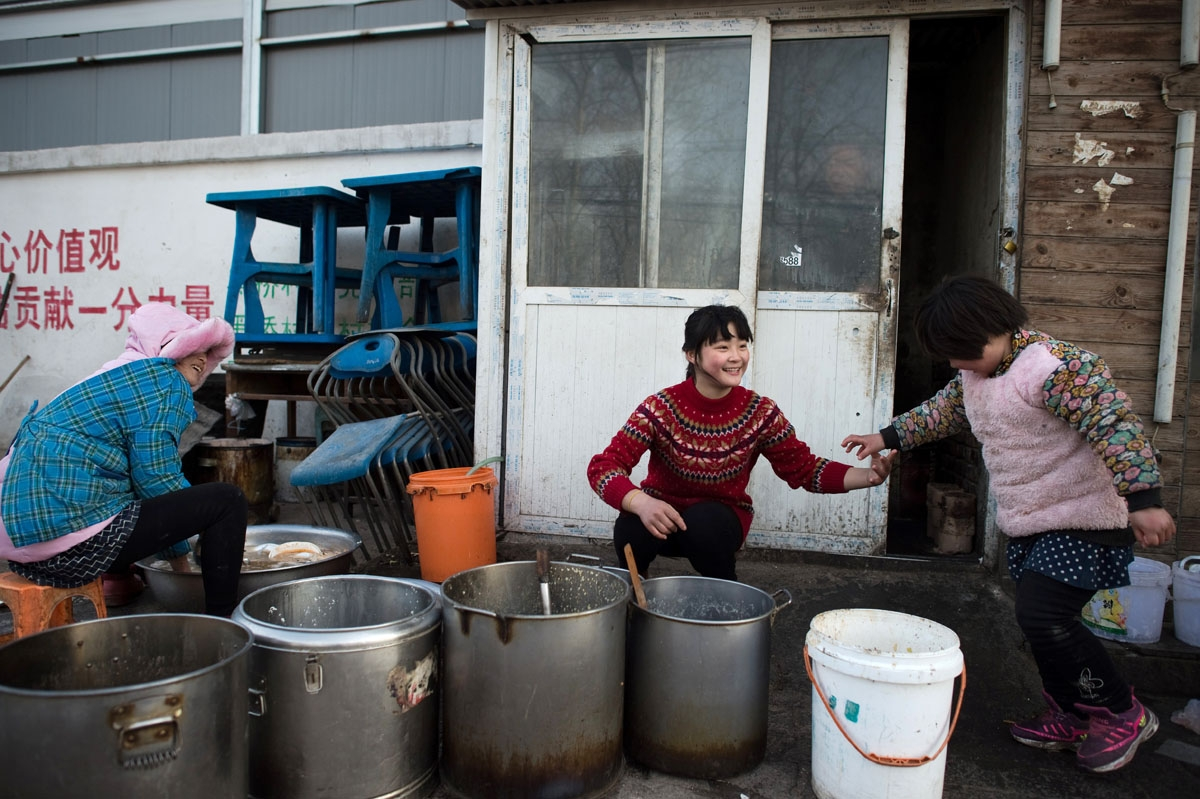 This picture taken on January 18, 2017 shows workers cleaning dishes outside a restaurant in the Heiqiaocun migrant village in Beijing.