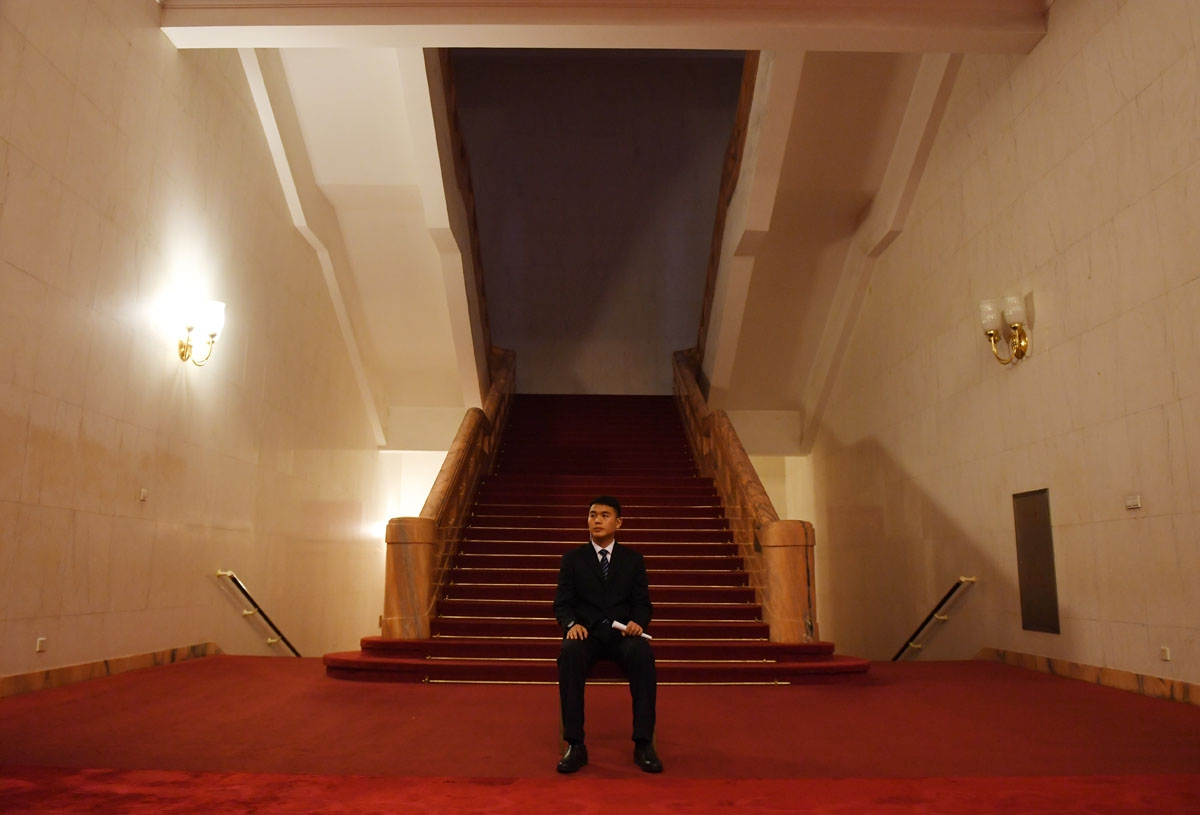 A security guard sits below a stairwell in the Great Hall of the People near the venue where Hong Kong delegates were meeting during the National People's Congress in Beijing on March 7, 2017.