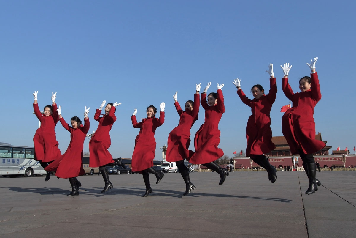 Hostesses jump as they pose for a picture during the opening of the National People's Congress in Beijing on March 5, 2017. China's rubber-stamp congress opened on March 5 in an annual pageant of Communist-controlled democracy.