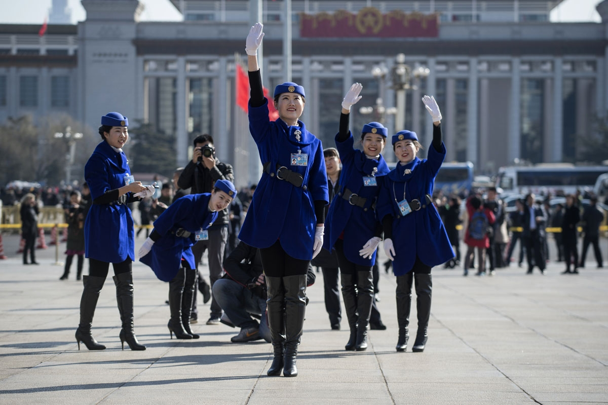 Hostesses pose for a picture in front of the Great Hall of the People during the opening of the National People's Congress in Beijing on March 5, 2017.