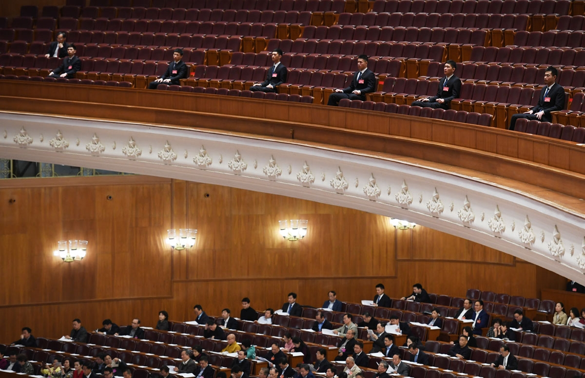 Security guards sit on a balcony above delegates during a plenary session of the Chinese People's Political Consultative Conference (CPPCC) at the Great Hall of the People in Beijing on March 10, 2017.