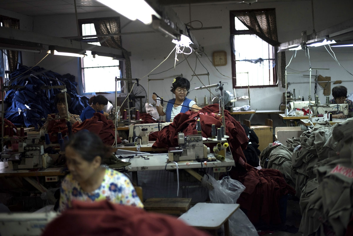 In this picture taken on September 8, 2016, workers prepare sew t-shirts in a factory in Zhujiajiao, on the outskirts of Shanghai.