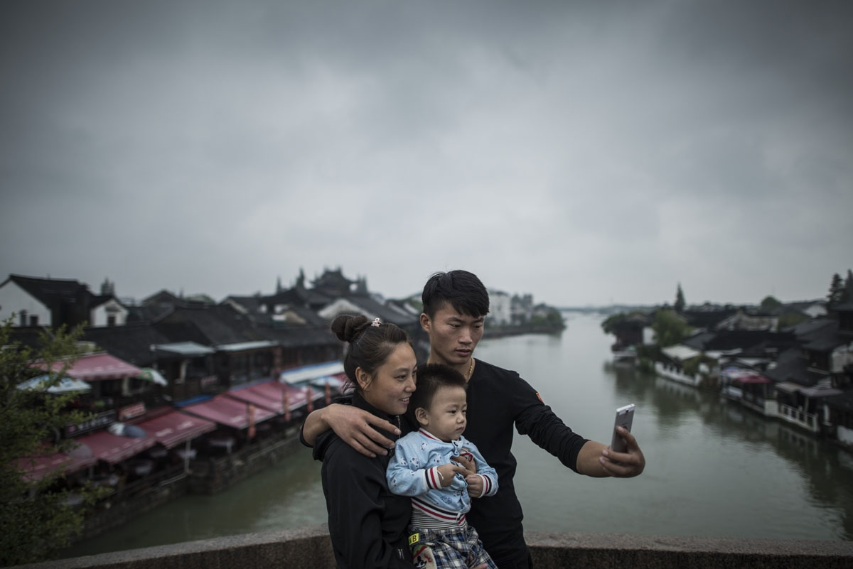 A man with his wife and his son pose for a picture in Zhujiajiao, on the outskirts of Shanghai, on September 7, 2016