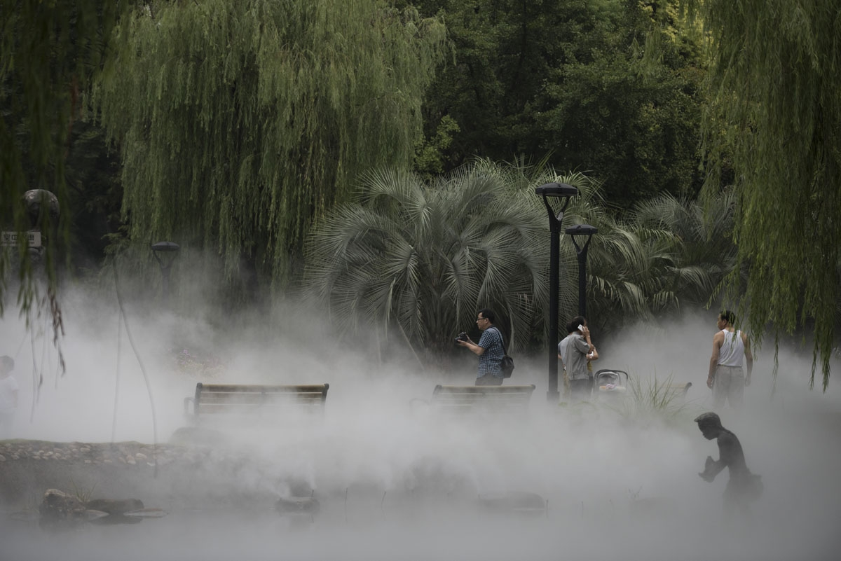 People take pictures of water spraying in Mengqinyuan park in Shanghai on September 11, 2016